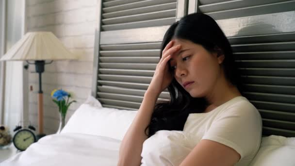 Sick Asian Young Woman Feeling Bad Sitting Her Bed ⬇ Video by ©  primagefactory Stock Footage #194959440