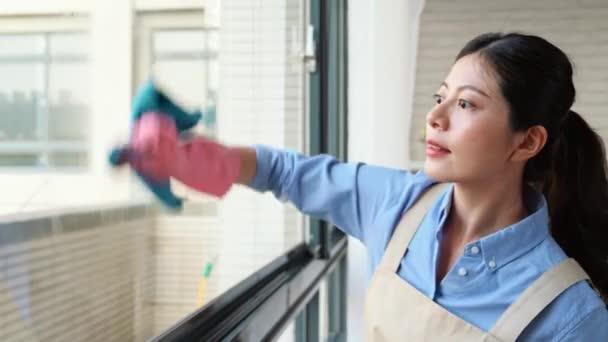 Frühling Putzfrau sauber Fenster mit Gummihandschuhen, Lappen und Reinigungsmittel während täglich sauber zu Hause