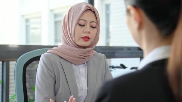 two of business people having the job interview. female candidate communicating together with the company female Muslim manager