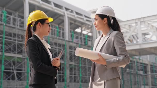Professional Asian female engineers are shaking hands and smiling. businesswoman standing near the building and looking at each other with trust.