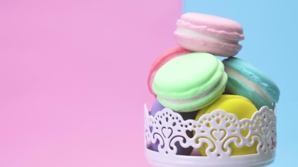 Šest barevných makronky naskládané v šálku a otočit na pravé straně od výrazných pastelových pozadí