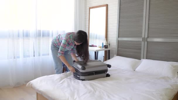 Asian woman finishes packaging and zipping up the suitcase. She is ready for the amazing trip.