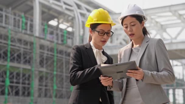dva mladí profesionální stavební inženýři diskuse s architekty na staveništi nebo stavbě nová dominanta s digitální tabletový počítač