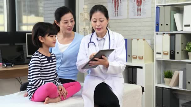 young beautiful Asian female doctor showing digital tablet to talking about the health condition of the kid to the family.