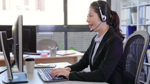 Call center business woman talking on headset. Asian female in customer service position talking on the phone.