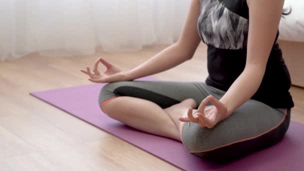 Close up shot of a lotus finger of female zen sitting on the floor doing meditation.