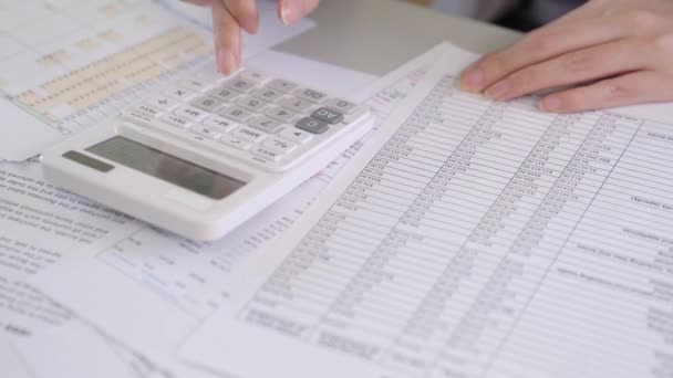 Businesswoman hand analyzing report on chart with calculator in office
