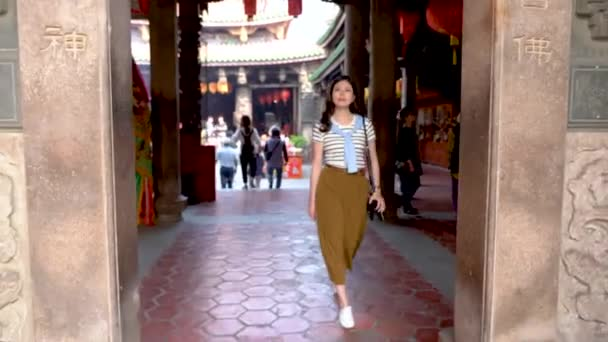 CHANGHUA, TAIWAN - MARCH 26, 2018: Asian woman walked passed the entrance and the camera.