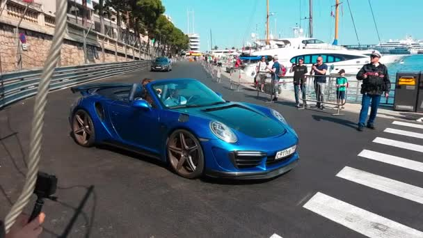 Monte-Carlo, Monaco-2018. április 21.: Férfi vezetés egy kék Topcar Stinger Gtr Porsche 911 Turbo Cabriolet 2018 az úton, a Monaco F1 Grand Prix Circuit (Port Hercules-től), az induló és a gyors gyorsulások - 4 k videóinak