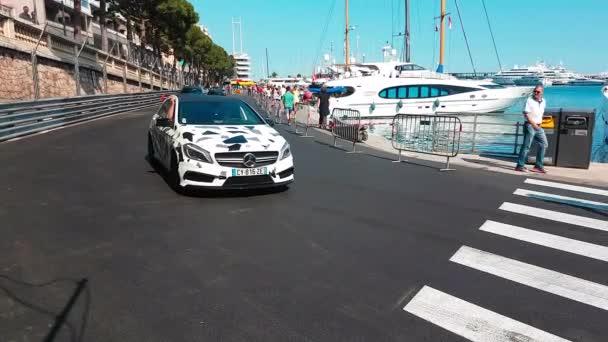 Monte-Carlo, Monaco-2018. április 21.: Férfi fehér Mercedes-Benz A45-Amg vezetői 360 Hp az úton a Monaco F1 Grand Prix Circuit (Port Hercules), francia Riviéra - 4 k videóinak