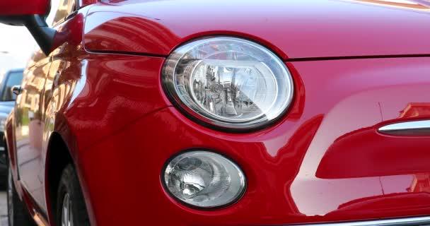 kleiner roter italienischer Kleinwagen, der auf der straße in italien geparkt ist. Frontlicht-Detail, abstrakte Reflexion auf glänzender Karosserie. Nahaufnahme - dci 4k resolution