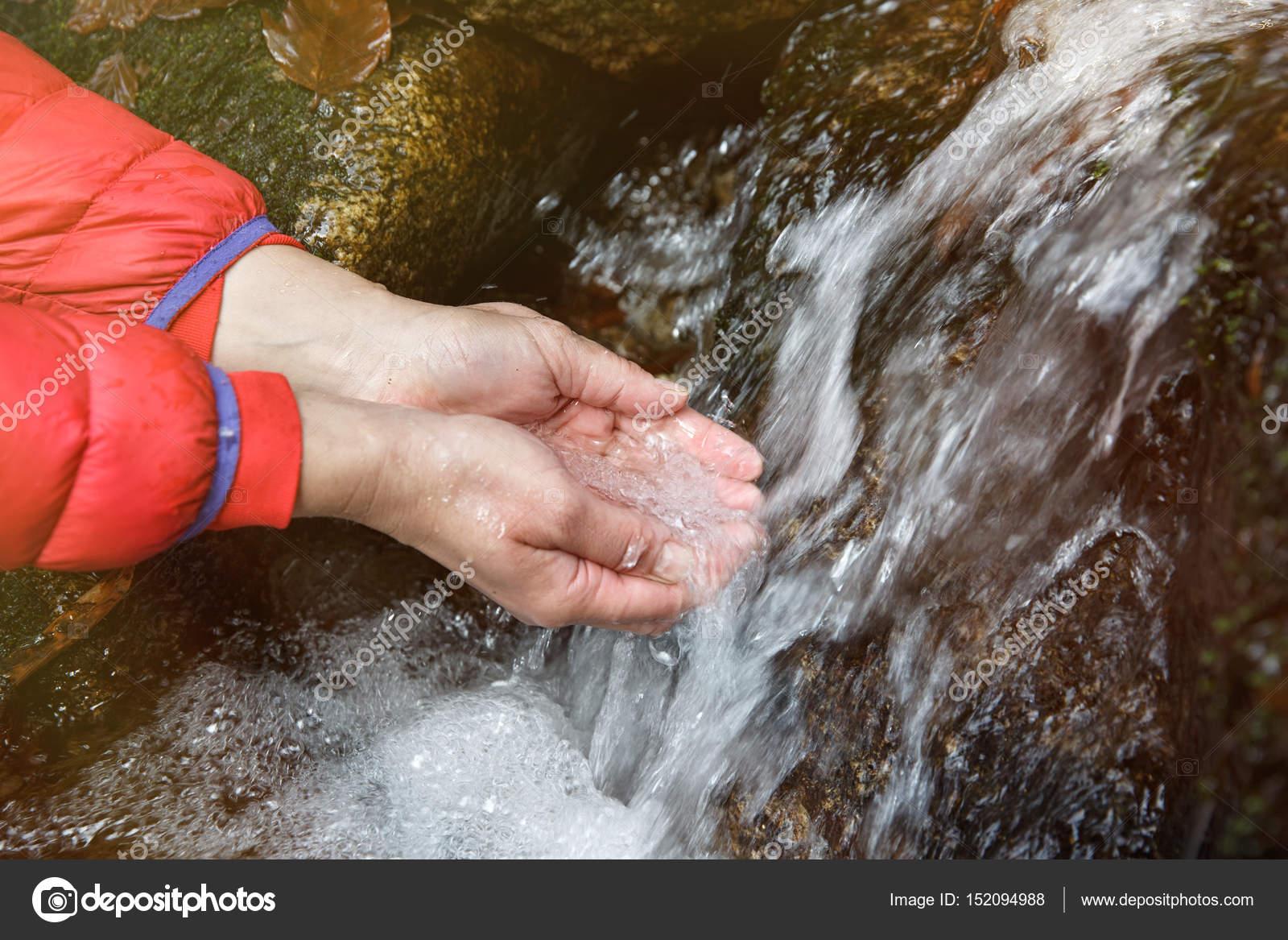 Excursionista sediento bebiendo agua de un manantial cristalino ...