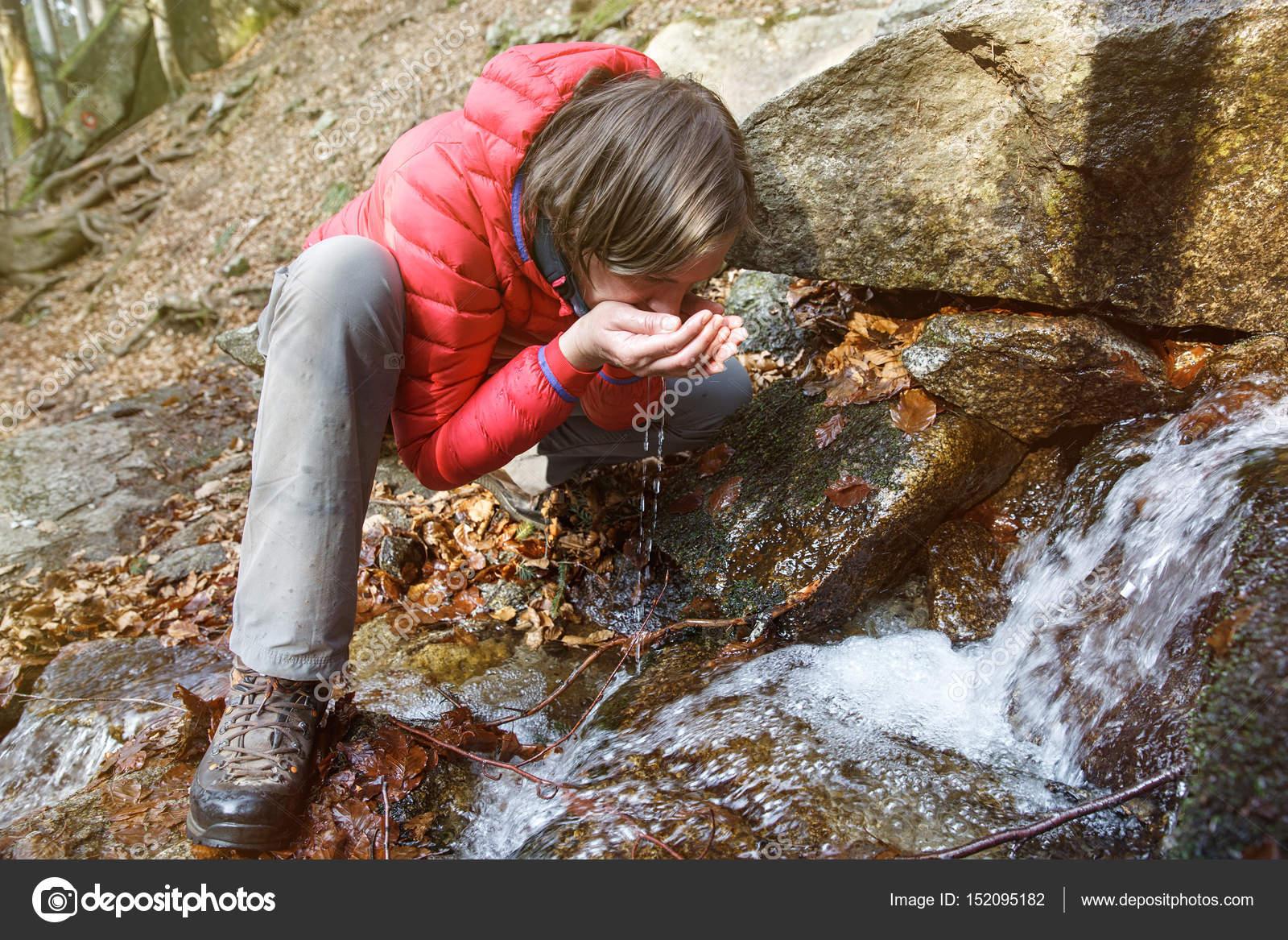 Excursionista sediento bebiendo agua de un manantial ...