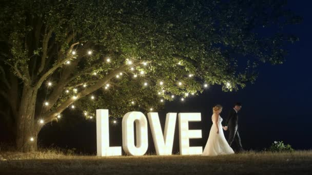 Young couple in love in evening dresses are going from love light letters.