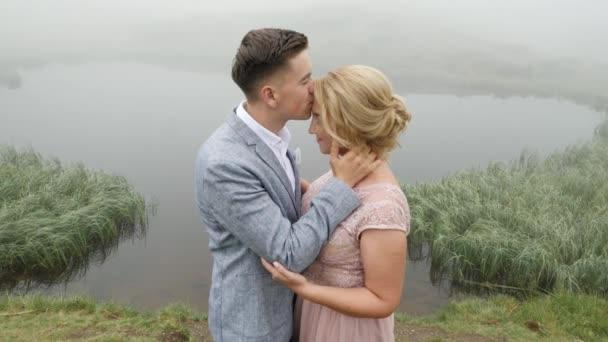 Člověk políbí dívku u jezera v pozadí mlha