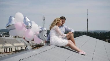 Young couple sitting on the roof with balloons.