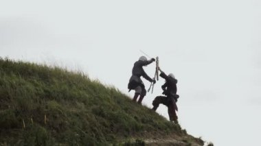 Two warriors Viking are fighting with swords and shields.
