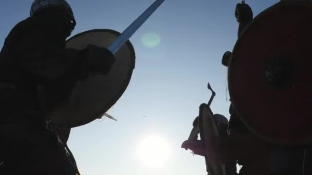 Silhouettes of Vikings warriors fighting with swords, shields. Contre-jour