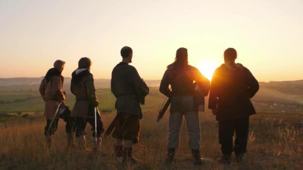 Bojovníci Vikingové stojí v poli a podívejte se na krásný západ slunce na bitevním poli