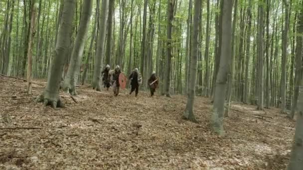 Warriors of Vikings are running in the forest on the battle.