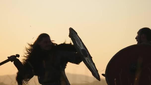Siluety válečníků Viking bojují s meči a štíty. Contre-jour