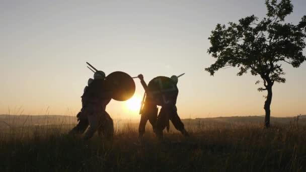 Siluety bojovníků Vikingy, nebo bojovat s meči, štíty. Contre-jour