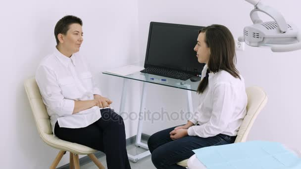 Dentist talking with young female patient in at the dentist clinic.