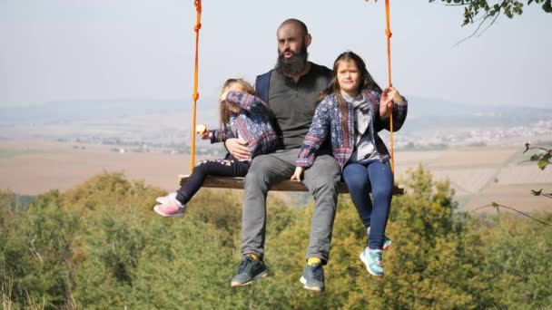 Dad swinging with daughters on a swing under a tree.