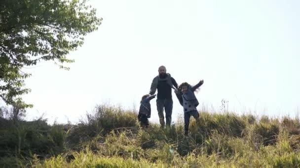 Otec s jeho dvě dcery, které běží z kopce na kameru.