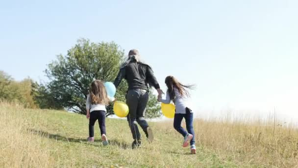 Father with his two daughters with an air balloons running to up on the hill