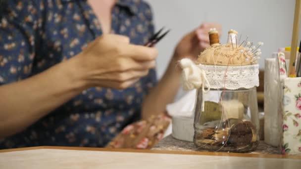 Žena, šití panenku. Bere nůžky a řezání. Detail