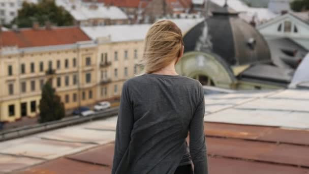 Drunk woman drinks alcohol and going to the brink of roof. Wind blowing hair.
