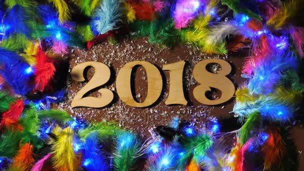 Čísla roku 2018 na hnědé pozadí s barevné peří a blikající věnec