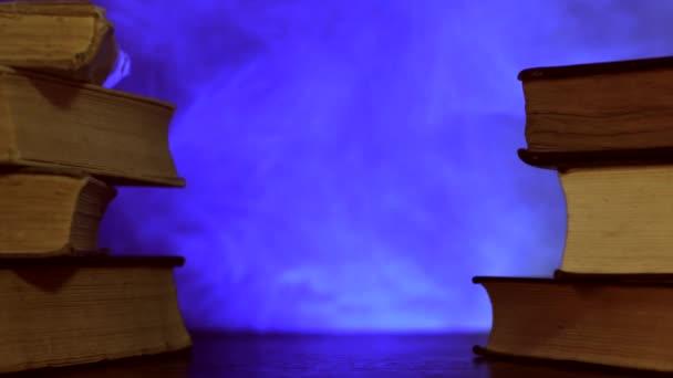 Hromádky knih stojí u hořící svíčky a barevný kouzelný kouř létá.
