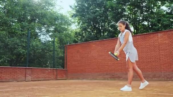 Tenistka cvičí svou techniku servírování na tréninku