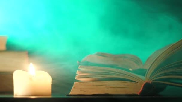Poblíž otevřené knihy hoří svíčka a lítá barevný magický kouř.