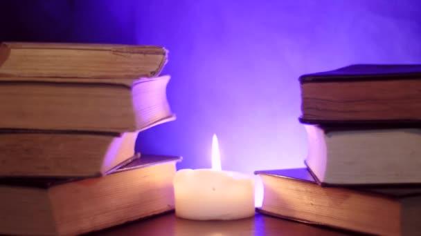 Stapel von Büchern stehen neben einer brennenden Kerze und farbiger Zauberrauch steigt auf..