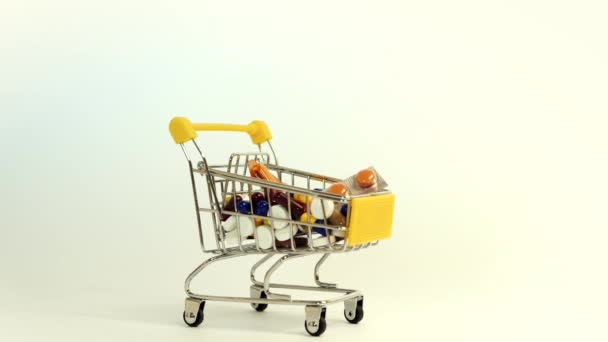 Supermarket trolley filled with medical capsules on a white background