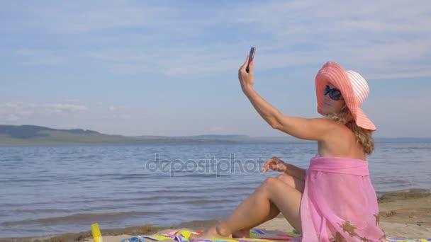 Frau mit Handy am Strand.