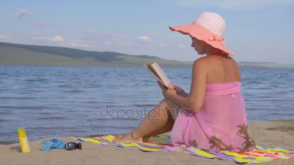 Frau am Strand liest ein Buch.