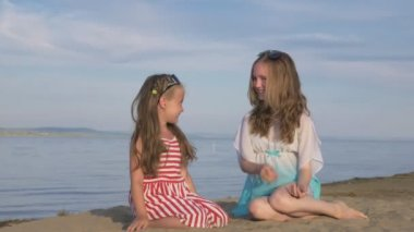 Two teenage children are sitting on the beach.