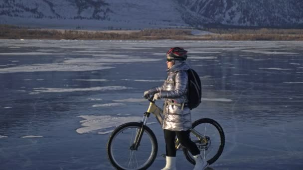 Žena je jízda kole na ledě. Dívka je oblečená v stříbřitě péřová bunda, Cyklistika helma a batoh. Ledem zamrzlé jezero Bajkal. Pneumatiky na kole jsou pokryty speciální hroty.