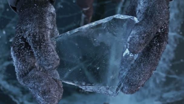 Der Mann in den Handschuhen zertrümmert das Eis auf dem Eis. Zeitlupe. bewegt sich die Kamera hinter dem Eis. ein Stück Eis ist sehr schön über das Eis mit magischen Rissen gebrochen. Partikel gefrorenen Wassers.