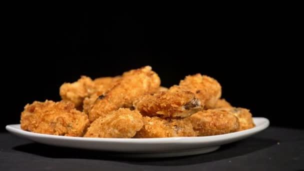 Hűvös gyönyörű friss lédús főtt csirke szárny költő forgatni a lemezjátszó. Bivaly szárnyak elterjedt az élelmiszer, az fehér lapot. Nagyon finom és szép. Főzés olajsütő fry gép.