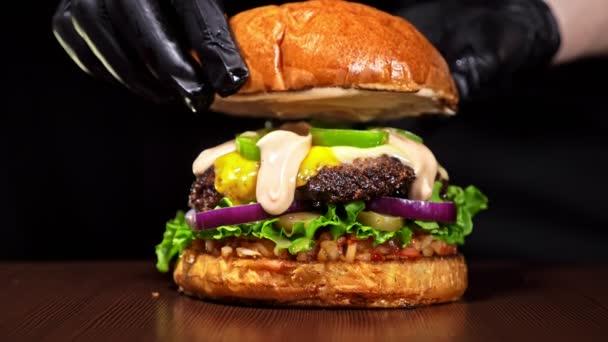 Vaření Burger na černém pozadí v černé potravinářské rukavice. Velmi lahodný vzduch bun a mramorovým hovězí. Restaurace, kde je každá karbanátky vařené ručně. Nebyly ideální. Vypadají opravdově, milující ručně vyrobené.