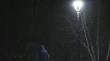 The man in the street light. Its snowing against the background of lamp. Slow motion in 180 fps. Snowflakes beautifully fall. The man is dressed in a cool black coat.