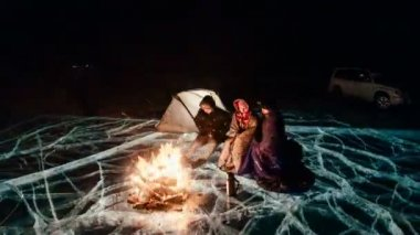 Three travelers by the fire right on the ice at night. Campground ice. The tent stands next to the fire. People are warming themselves by the fire. Time-lapse with a circular motion. The Lake Baikal.