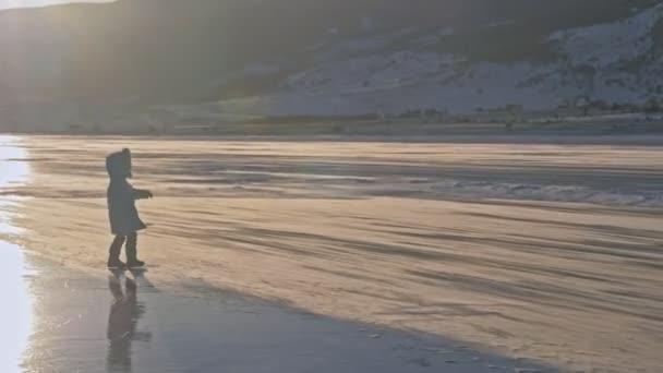 Mädchen geht auf Eis. Kind auf Eis im Schneesturm. Schnee fliegt über die Eisfläche. Schneeflocken fliegen auf dem Eis des Baikalsees. Hintergrund-Ansicht Berglandschaft.