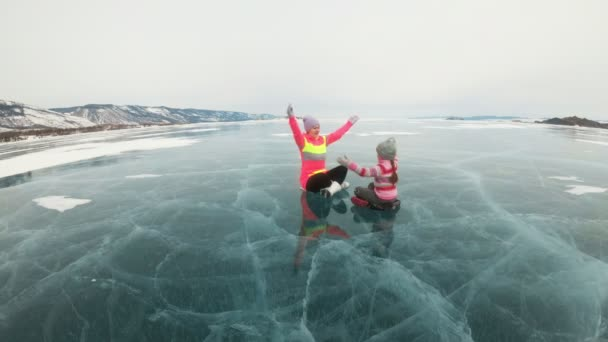 Family is training practice yoga in winter. Woman is do stretching and meditation on ice in nature. Mother and daughter practices yoga on ice in cracks. Girls do sport fitness in outdoor.