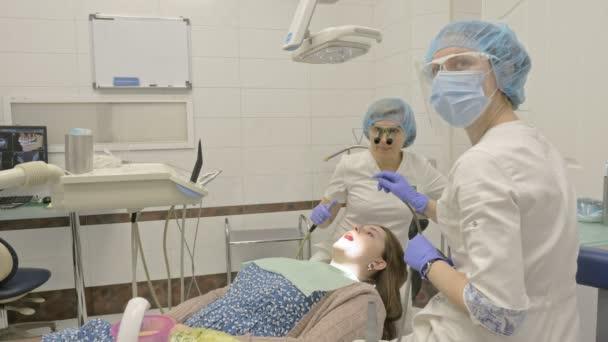Žena na zubní klinice dostane zubní ošetření k vyplnění dutiny v zub. Zubní plomba a kompozitní materiál polymerizační Uv světlem a laserem
